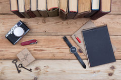 Top view on wooden desktop with books, camera, watch and gift bo Stock Images