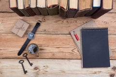 Top view on wooden desktop with books, keys, watch, notepad and