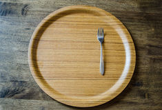 Top view of wooden dish and fork on weathered wooden background Royalty Free Stock Photography