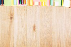 Wooden office desktop with colorful supplies. Top view of wooden office desktop with colorful supplies and copy space. Design and art concept Royalty Free Stock Image