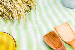 Top view of wooden spoon, yellow glass plate and ear of rice on Stock Photography