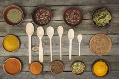 Wooden spoons among bowls with spices Stock Photo