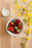 Top view of a wooden table with flower decoration, bowl of delicious red and fresh strawberries and a small bowl of fresh cheese Royalty Free Stock Photo