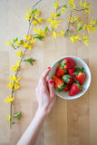 Top view of a wooden table with flower decoration and a woman's hand reaching for a bowl of delicious fresh strawberries Stock Photos