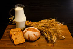 Top view on a wooden table with a jug of milk, rye bread and a sheaf Stock Images