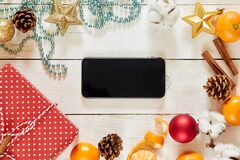 Table with phone and Christmas decorations. mockup