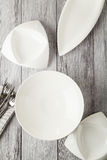 Top view wooden table setting with copyspace. Four designed plates with knives and forks Stock Image