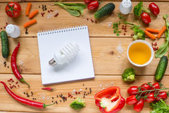 Top view of wooden table with space, healthy eating concept. Table with white notebook and Variety of fresh vegetables, tomato, pepper, cucumber, carrot, space Royalty Free Stock Photo