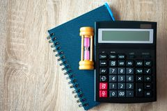 Top view of wooden work desk with note book, calculator and hou. R glass stock photo