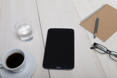 Top view of a wooden work desk with tablet pc notebook glasses g Stock Images