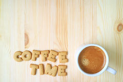 Top view of the word COFFEE TIME spelling with alphabet shaped biscuits, and a cup of coffee on wooden table with free space for t. Ext and design Stock Image