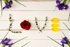 Top view of word love made from floral elements and beautiful iris flowers. On wooden surface royalty free stock images