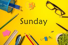 Top view of word SUNDAY and different office supplies on yellow table background. Business Concept of work day Royalty Free Stock Images