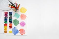 Top view of Work Process Blank Watercolor Paper pad, Watercolor Painting Supplies, Brushes and Colorful Pencil. Creation process o. F watercolor painting Stock Photo