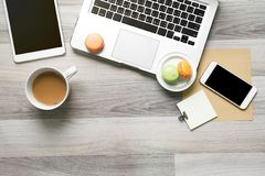 Top view of work space with macaron and coffee for time break. Top view of work space with macaron and coffee for time break, laptop, tablet computer Royalty Free Stock Images