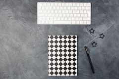 Top view of work space office desk black background with paper notebook copybook, keyboard, pen and clips. Copy space stock image