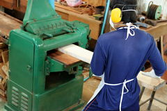 Top view,Worker is working with planing of wood machine.He is wearing safety equipment in factory Royalty Free Stock Photos
