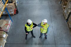 Top view workers with face mask greeting indoors in warehouse, coronavirus concept.