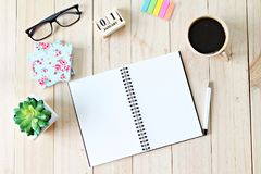 Top view of working desk with blank notebook with pen, coffee cup, colorful note pad, cube calendar and eyeglasses on wooden backg. Still life, business office Royalty Free Stock Photography