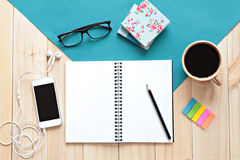 Top view of working desk with blank notebook with pencil, coffee cup, colorful note pad, eyeglasses and mobile phone on wooden bac Royalty Free Stock Image