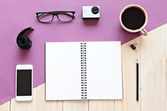 Top view of working desk with blank notebook with pencil, coffee cup, eyeglasses, mobile phone and action camera on wooden backgro Royalty Free Stock Image