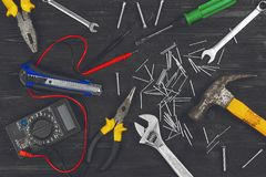 Top view on working hand tools,wrench, screwdriver, pliers, hammer, adjustable spanner, office knife, scattered nails and screws. stock images