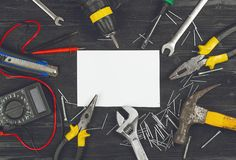 Top view on working hand tools,wrench, screwdriver, pliers, hammer, adjustable spanner, office knife, scattered nails and screws. Royalty Free Stock Image