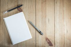 Top view of working object : gray pencil and black pen near white notebook on wood table. Gray pencil and black pen near white notebook on wooden table Stock Photography