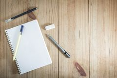 Top view of working object : gray pencil and black pen near white notebook on wooden table. Gray pencil and black pen near white notebook on wooden table Stock Photos