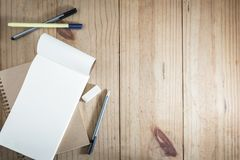 Top view of working object : gray pencil and black pen near white notebook on wooden table. Gray pencil and black pen near white notebook on wooden table Royalty Free Stock Images