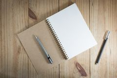 Top view of working object : gray pencil on brown and white notebook and black pen on wooden table. Gray pencil on brown and white notebook and black pen on Royalty Free Stock Photography