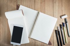 Top view of working object : gray pencil and many black pen on wooden table and smartphone on white notebook. Gray pencil and many black pen on wooden table and Royalty Free Stock Images