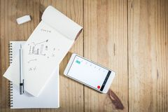 Top view of working object : gray pencil on notebook and white smartphone open calendar on wooden table Royalty Free Stock Photography