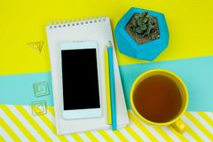 Working place with coffe, succulent, notebook and smartphone with blank black screen. Top view working place with coffe, succulent, notebook and smartphone with royalty free stock photos