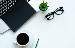 Top view working space with laptop, flower, cup of coffee , notebook, pen and glasses stock images