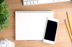 Top view of working space with smartphone over a blank notepad Stock Photos