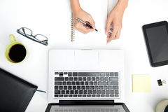 Top view of working table with hand writing on notebook Royalty Free Stock Images