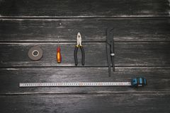 Top view of Working tools - screwdriver, adjustable wrench, pliers, duct tape and tape measure on the wooden background. Concept stock image