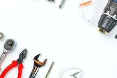 Top view of Working tools,wrench,socket wrench,hammer,screwdrive. R,plier,electric drill,tape measure,machinist square and safety glasses on white background Royalty Free Stock Images