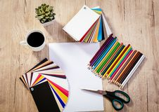 Top View Workplace Artist Designer. Top view of a designer workspace with blank paper and pallete color. Different office accessories and cup of coffee is on the royalty free stock images