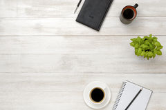 Top view workplace with cup of coffee, pot plant, notebook, pencil and pen on wooden table Stock Photos