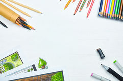 Top view of workplace of a designer with copyspace. Sketching tools: liners, markers, sketch images and pencils on a creative tabletop. Place for text Stock Images