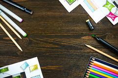 Top view of workplace of a designer with copyspace. Sketching tools: liners, markers, sketch images and pencils on a creative wooden tabletop. Place for text Stock Photos
