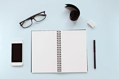 Top view of workspace desk with blank notebook, eye glasses, smart phone, ribbon and office stationery on blue background Stock Photos