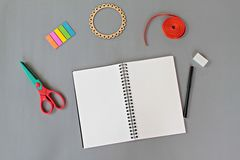 Top view of workspace desk with blank notebook and office stationery set on gray background Stock Photos
