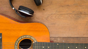 Top view workspace with headphone and acoustic guitar on wooden. Table background .Free space for your text Stock Image