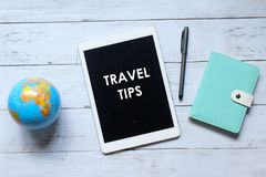 Top view of world globe,notebook,pen and tablet pc written with TRAVEL TIPS on wooden background.  royalty free stock photo