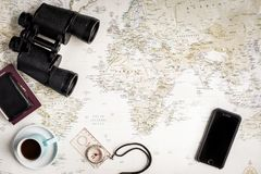 Top view map and travel planning items. Top view of a world map with a few items scattered around. Binoculars, Compass, mobile phone, wallet, passport and a cup Royalty Free Stock Images