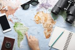 Top view of world map, sunglasses, binocular and passport with texting space. Travelling concept, plan a trip, Itinerary planner, one hand point to the map stock images
