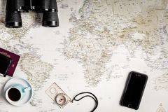 Top View of a world map for travel and adventure planning. With scattered items: Compass, binoculars, coffee, mobile phone Stock Images